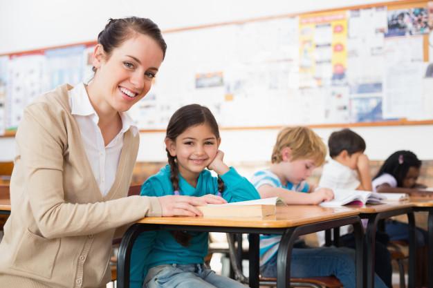 pretty-teacher-helping-pupil-classroom_13339-69092